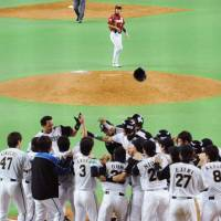 Party time: The Fighters gather at home plate to celebrate Terrmel Sledge's game-winning grand slam in the bottom of the ninth inning against the Eagles at Sapporo Dome on Wednesday.   KYODO PHOTO