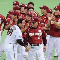 Touch of class: Fighters skipper Masataka Nashida greets Eagles manager Katsuya Nomura after Saturday's game. | KYODO PHOTO