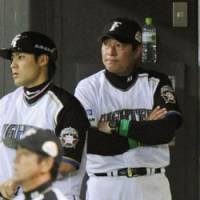 On the job: Fighters manager Masataka Nashida (right) faces a difficult decision in giving star hurler Yu Darvish, who has been sidelined throughout the playoffs, the OK to pitch in the Japan Series or not. | KYODO PHOTO