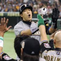Hero: The Fighters' Shinji Takahashi returns to the dugout to cheers from teammates after hitting a solo home run in the fifth inning of Game 4 of the Japan Series on Wednesday. | KYODO PHOTO