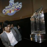 On the road: A visitor to Tokyo's MLB Cafe takes a closer look at the World Series trophy on Monday. | AP PHOTO