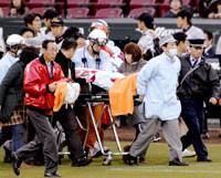 Cause for concern: Takuya Kimura, the Yomiuri Giants infield and running coach, is taken off the field on a stretcher after collapsing on Friday before the game at Mazda Stadium. | KYODO PHOTO