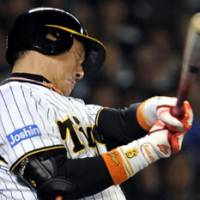 Special feat: Tigers slugger Tomoaki Kanemoto belts a two-run homer off Giants pitcher Shugo Fujii in the sixth inning on Tuesday at Koshien Stadium. It was the 444th home run of Kanemoto's career, tying him with Shigeo Nagashima for 13th place on Japan's all-time home-run list. | KYODO PHOTO