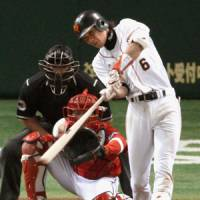 Hayato Sakamoto of the Giants connects for a three-run homer during the eighth inning of Friday's game against the Hiroshima Carp at Tokyo Dome. Yomiuri won 10-4.