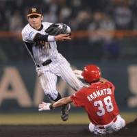 Steady defense: Tigers shortstop Takashi Toritani throws the ball to first base to complete a sixth-inning double play as Carp baserunner Masato Akamatsu tries to disrupt his timing at Koshien Stadium on Friday. Hanshin beat Hiroshima 10-6. | KYODO PHOTO