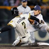 Not fast enough: Hanshin baserunner Shunsuke Fujikawa is tagged out by Seibu infielder Yasuyuki Kataoka as he attempts to steal second in the fifth inning on Wednesday at Koshien Stadium. The Lions won 3-1.   KYODO PHOTO