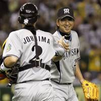 Series-opening win: Tigers catcher Kenji Johjima congratulates closer Kyuji Fujikawa after the team's 10-8 victory over the Giants on Friday at Tokyo Dome. | KYODO PHOTOS