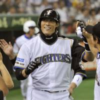 Home run smile: Hokkaido Nippon Ham's Yoshio Itoi returns to the dugout after cracking a two-run blast in the first inning against Softbank on Thursday night at Tokyo Dome.   KYODO PHOTO