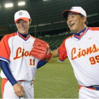 That winning feeling: Lions pitcher Masamitsu Hirano (left) and manager Hisanobu Watanabe share a light-hearted moment after the team's 7-0 victory over the Fighters on Thursday at Seibu Dome. | KYODO PHOTOS