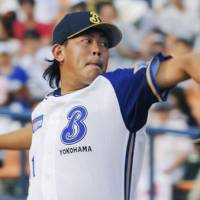 Solid relief: BayStars closer Shun Yamaguchi tosses two scoreless innings against the Giants on Saturday afternoon at Yokohama Stadium. Yokohama defeated Yomiuri 7-5. | KYODO PHOTO
