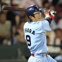 On the attack: Swallows outfielder Yasushi Iihara slugs a game-tying solo home run in the ninth inning against the Carp on Tuesday at Mazda Stadium. Hiroshima defeated Tokyo Yakult 2-1 in 10 innings. | KYODO PHOTO