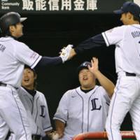 Good job, buddy: Seibu outfielder Tomoaki Sato (left) exchanges a high-five with starter Fumiya Nishiguchi as he comes back to the bench after hitting an RBI single and scoring in the sixth inning on Thursday at Seibu Dome. The Lions shut out the Orix Buffaloes 3-0. | KYODO PHOTO