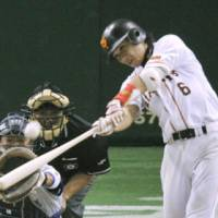 Star of the night: The Giants' Hayato Sakamoto celebrates his game-winning home run in the 12th inning against the BayStars on Tuesday at Tokyo Dome. Sakamoto (below) hits his 30th homer of the season into the left-field stands, leading Yomiuri to a 4-3 win over Yokohama. | KYODO PHOTO