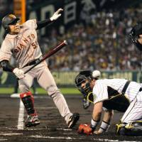 Ouch: Yomiuri Giants second baseman Shigeyuki Furuki is hit by a pitch with the bases loaded while Hanshin Tigers catcher Kenji Johjima looks on in the first inning at Koshien Stadium on Tuesday. The Giants won 7-5. | KYODO PHOTO