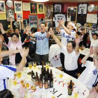 Banzai moment: Chunichi fans celebrate at a Chinese restaurant in Nagoya as the Dragons clinched the Central League regular-season title with the Hanshin Tigers' 5-0 loss on Friday. | KYODO PHOTO