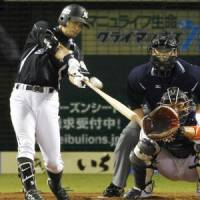 Textbook swing: Kazuya Fukuura's solo shot in the 11th inning carries the Chiba Lotte Marines to a come-from-behind 6-5 win over the Seibu Lions on Saturday. | KYODO PHOTO