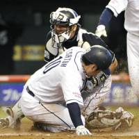 Iron man: Chiba Lotte's Tomoya Satozaki blocks the plate to prevent a run by Seibu's Tomoaki Sato on Sunday. | KYODO PHOTO