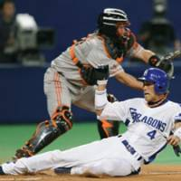 Safe at home: The Dragons' Atsushi Fujii scores the game's first run, beating the throw to Giants catcher Shinnosuke Abe in the second inning on Thursday in Game 2 of the Central League Climax Series final stage. Chunichi beat Yomiuri 2-0. | KYODO PHOTOS