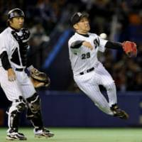 Not quick enough: Chiba Lotte reliever Shingo Ono makes a leaping throw to first while catcher Tomoya Satozaki looks on in the fifth inning in Game 4 of the Japan Series on Wednesday at Chiba Marine Stadium. The batter, Chunichi's Motonobu Tanishige, reached base safely. | KYODO PHOTO