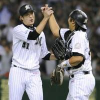 Job well done: Chiba Lotte closer Hiroyuki Kobayashi (left) and catcher Tomoya Satozaki celebrate the team's 3-0 win over the SK Wyverns in the Japan-Korea Club Championship on Saturday at Tokyo Dome. | KYODO PHOTO