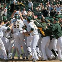 Walkoff knock: Oakland's Hideki Matsui jumps on home plate after hitting a game-winning solo home run in the bottom of the 10th inning against Texas on Sunday. The A's beat the Rangers 5-4. | KYODO
