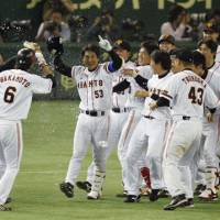 Celebration time: Teammates mob the Giants' Kazunari Sanematsu (53) after his walk-off single in the ninth inning against the Tigers on Wednesday at Tokyo Dome. Yomiuri defeated Hanshin 4-3. | KYODO