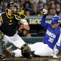 Safe at home: The Dragons' Masahiko Morino scores a run in the fourth inning as Tigers catcher Kenji Johjima waits for the ball during Friday's game at Koshien Stadium. Chunichi defeated Hanshin 4-2. | KYODO PHOTO