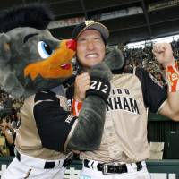 Bear hug: Fighters second baseman Kenshi Sugiya celebrates with the Fighters' mascot after his team's victory over the Seibu Lions on Saturday. | KYODO PHOTO