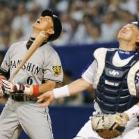 What's up: Tigers batter Tomoaki Kanemoto and Dragons catcher Kohei Oda watch a ball hit by Kanemoto during the fifth inning on Wednesday in Nagoya. The Dragons won 5-3. | KYODO