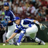 No time to waste: Chunichi catcher Keiji Oyama reaches for the ball after making an error against the Carp on Sunday. | KYODO