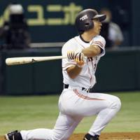 Giants star Michihiro Ogasawara bashes a solo home run in the second inning against the Swallows on Friday.