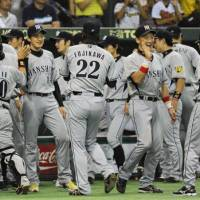 Thrill of victory: The Hanshin Tigers celebrate their 2-1 win over the rival Yomiuri Giants on Wednesday at Tokyo Dome.   KYODO