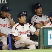 Not pleased: Tokyo Yakult Swallows coach Tetsuya Iida (front) and manager Junji Ogawa (80) watch their team fall 6-1 to the Yomiuri Giants on Tuesday at Tokyo Dome. | KYODO