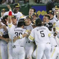 All for one: Hawks players give manager Koji Akiyama the traditional doage (victory toss) after the Pacific League champions advanced to the Japan Series by beating the Seibu Lions in 12 innings on Saturday. | KYODO PHOTO
