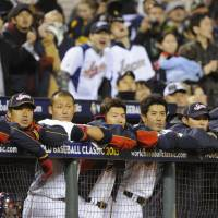 Disappointment: Japan players watch the action on the field in the sixth inning against Puerto Rico on Sunday in San Francisco. | KYODO