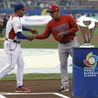 Let's be friends: Dominican Republic manager Tony Pena (left) and Puerto Rico counterpart Edwin Rodriguez shake hands before the World Baseball Classic final on Tuesday. | AP