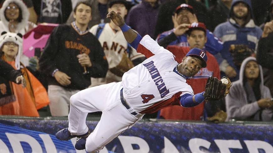 Leap of faith: The Dominican Republic's Miguel Tejada catches a foul ball in the seventh inning of his team's 3-0 win over Puerto Rico in the World Baseball Classic championship game in San Francisco on Tuesday.