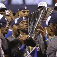 On top of the world: The Dominican Republic's Jose Reyes holds the World Baseball Classic trophy after beating Puerto Rico. | AP