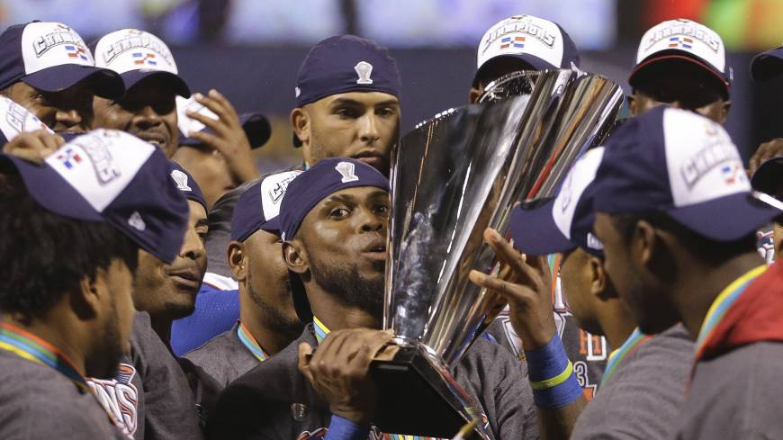 On top of the world: The Dominican Republic's Jose Reyes holds the World Baseball Classic trophy after beating Puerto Rico.