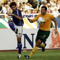 Yuki Abe, left, and Australia's Mark Viduka battle for the ball during the first half of their Asian Cup quarterfinal match on Saturday in Hanoi. Japan faces Saudi Arabia in the semifinals on Wednesday.   AP PHOTO
