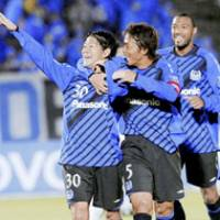 One-man effort: Gamba Osaka midfielder Masato Yamazaki (left) is congratulated by Satoshi Yamaguchi (5) and Lucas after scoring the second of his two goal against Australia's Melbourne Victory in their Group G match of the Asian Champions League on Wednesday at Expo Stadium in Osaka. Gamba won 2-0.   KYODO PHOTO