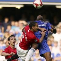 Meeting of the minds: Chelsea's Didier Drogba, right, and Manchester United's Rio Ferdinand vie for the ball during their match on Sunday at Stamford Bridge in London. The match ended 1-1. | AP PHOTOS