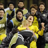 One step closer: Substitute Ryohei Hayashi hugs goalkeeper Takenori Sugeno as teammates rush on to the field Sunday following Kashiwa Reysol's win on penalties over Monterrey of Mexico. The team will face South American champions Santos in the semifinals on Wednesday. | KYODO PHOTO