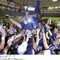 Never gets old: Obic Seagulls players toss linebacker Naoki Kosho in the air after their 38-28 victory over Kwansei Gakuin University in the 65th Rice Bowl on Tuesday at Tokyo Dome. | KYODO