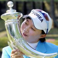 Kim Hyo Joo plants a kiss on her trophy following her victory at the Suntory Ladies Open on Sunday, making her the youngest ever title winner on the Japan LPGA Tour in the process. | KYODO