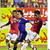 Japan Under-22 player Naohiro Ishikawa fights for the ball with two members of the Egyptian Under-22s during their match at the International Football Olympic Teams Championship.