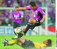 Daisuke Saito of Kyoto Purple Sanga avoids the tackle of a Kashiwa Reysol player during Saturday's J. League second-stage match at Kashiwa Stadium. Reysol won 2-1.