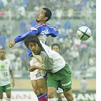 Yokohama forward Tatsuhiko Kubo (left) competes for the ball with Tokyo Verdy defender Kenta Togawa in a first-half action on Saturday at Tokyo's National Stadium. F. Marinos defeated Verdy 1-0.