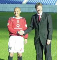 Japan midfielder Shinji Ono shakes hands with Urawa Reds head manager Buchwald after signing with the J. League club.