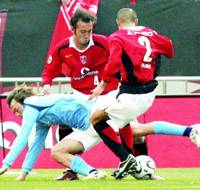 Marcus Tulio Tanaka (center) and Keisuke Tsuboi (right) of Urawa tackle Iwata's Bobby Cullen during their J. League Division One match in Saitama.